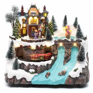 Pueblos navideños en miniatura: Paisaje navideño con música tren en movimiento y patinadores 25x25x15 cm