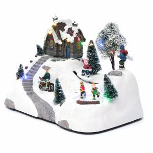 Christmas villages sets: Moving christmas scene with music and ice skating rink 20x30x15 cm